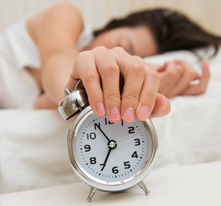 Person sleeping, with hand on alarm clock