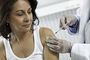 Health care provider giving woman injection in upper arm.