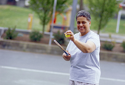 Photo of a middle aged woman getting ready to serve a tennis ball