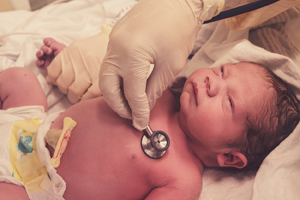 Checking newborn baby boy heart rate with a stethoscope.