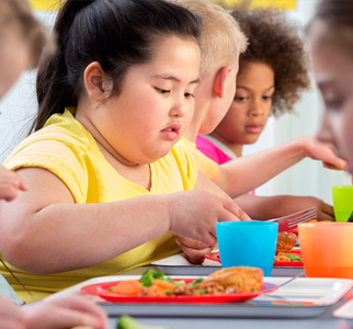Overweight child eating lunch at school