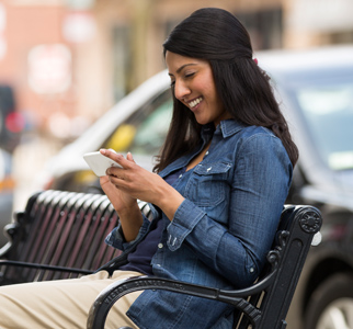 Woman sitting on park bench, looking at her cell phone
