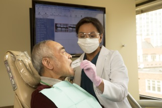 Dental professional working on man's mouth