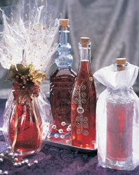 Decorateive bottles of red rosemary vinegar some wrapped in gift wrap.