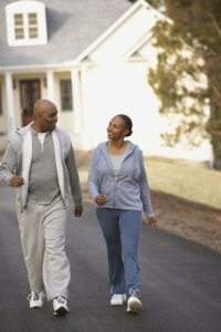 Photo of two older folks walking through a neighborhood